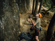 Man Belaying A Rock Climber At...