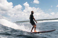 Skilled Surfer On Foamy Wave Looking At Camera On Surfboard