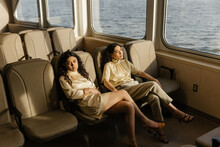Matching Sisters In Elegant Outfits Lounging In Sunlight On A Ferry Boat