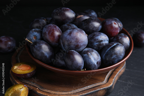 Slika na platnu Delicious ripe plums in bowl on black table