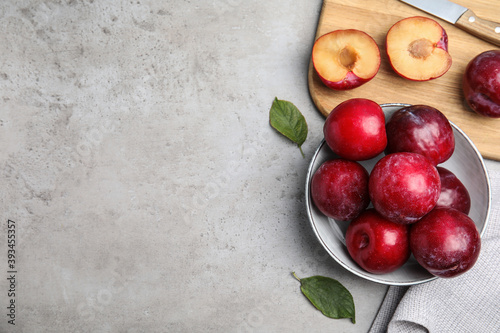 Tela Delicious ripe plums on grey table, flat lay. Space for text