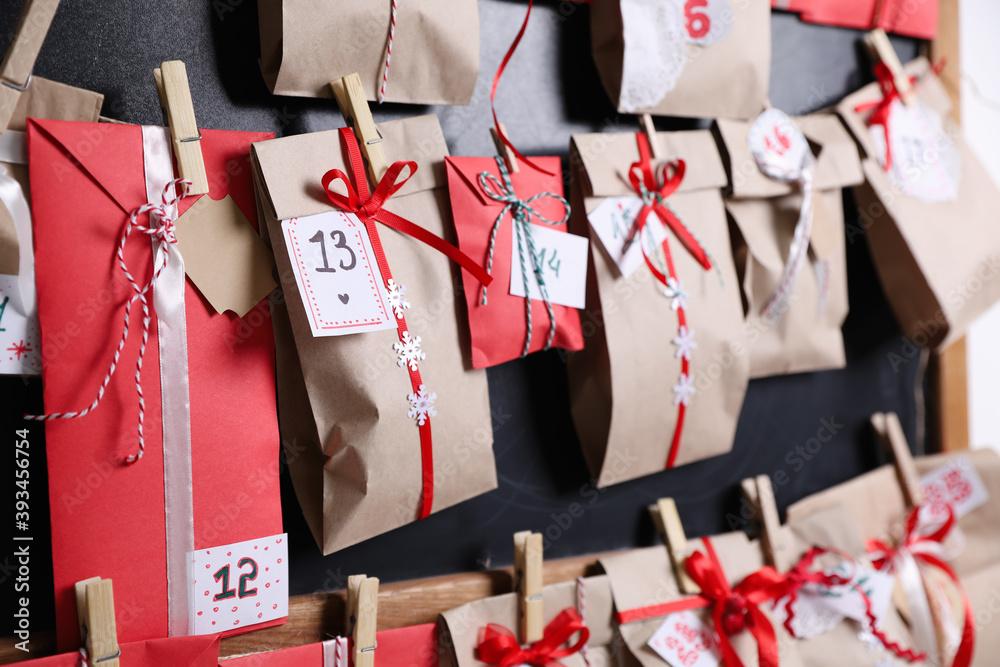Fototapeta Christmas advent calendar hanging on blackboard, closeup