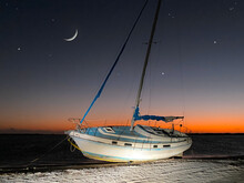 Sunken Sailboat Or Boat. Low Tide Of The Ocean. After Tropical Storm Or Hurricane. Florida Hurricane. Night Sky On Background.