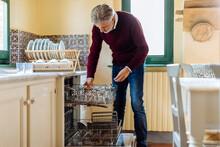 Adult Male Arranging Glasses In Dishwasher