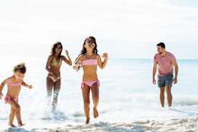 Happy Multiracial Family Enjoying Summer Holidays On Seashore