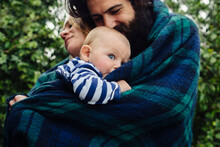Family Under Blanket In Garden
