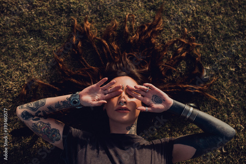 Canvas Print Trendy woman with tattoo and piercing hiding face with hands while chilling on l