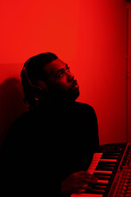 Young Man Playing Piano In Red Lights