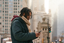 Black Man Using Smartphone On Street