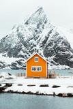 Colorful cabin near snowy mountain seashore