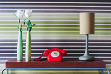 Old Fashioned Telephone With Lamp And Vases Of Tulips