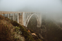 Majestic Arched Bridge Over Narrow River In Valley Against Foggy Highland In Overcast Weather