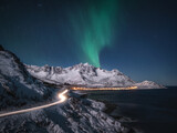 Northern lights and road leading to norwegian mountain peaks