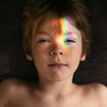 Little Boy With Rainbow Glare On His Face.