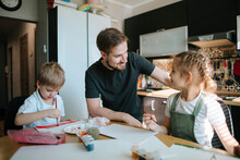 Young Father Teaches Drawing His Children.