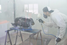 Male Motorcyclist Painting Tank With Spray Gun In Workshop
