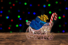 Decorative Sleigh With Blue Gift Boxes On A Bokeh Background. Space For Text.