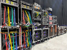 Backstage Area And Tech Zone With Rack Amplifiers, Signal Splitters, Flight Cases And Radio Microphone Systems. Professional Sound Equipment For A Concert.