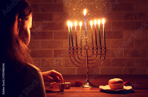 Fotografia Low key image of jewish holiday Hanukkah background with girl looking at menorah