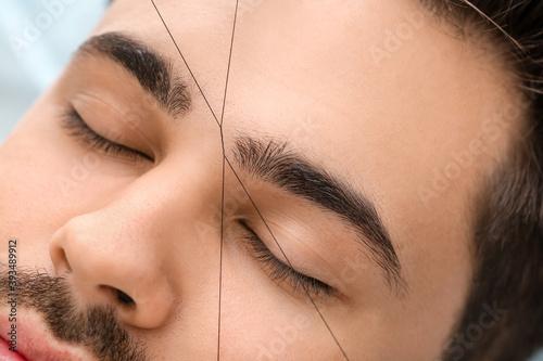Obraz na płótnie Young man undergoing eyebrow correction procedure in beauty salon, closeup