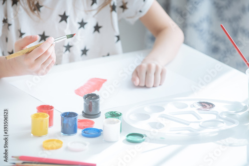 Photo a child in white clothes with stars sits at a white table holding a paintbrush in his hand