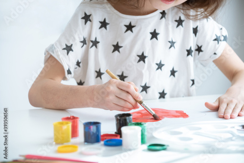 a child in white clothes with stars sits at a white table paints the heart red Wallpaper Mural
