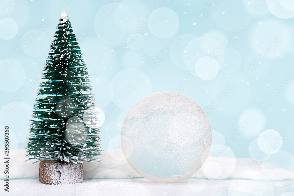 Fototapeta Christmas or New Year composition, decoration with glass ball snow globe and fir tree covered by snow on glitter background