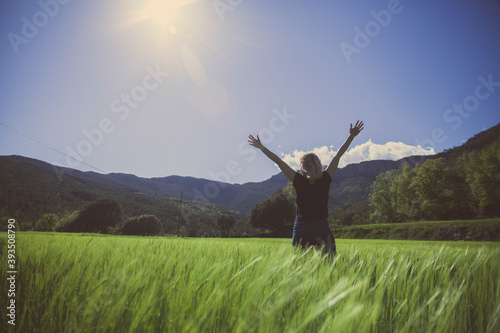 Tablou Canvas a girl with open arms in a green wheat field