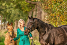 In The Golden Sun A Portrait Of A Blond Smiling Girl With Her Horse And Foal In The Forest. Wearing A Green Dress. Selective Focus