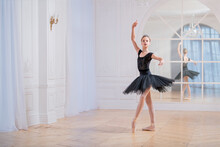 Young Ballerina In A Black Tutu Is Dancing On Pointe In Large Bright Hall In Front Of A Mirror.