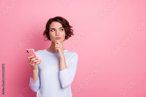 Minded girl use smartphone touch hand chin look copyspace think wear sweater iso Fotobehang