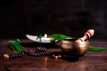 Close-up Of A Singing Bowl And Prayer Beads (mala) For Chanting Mantras As A Decoration On An Old Wooden Board