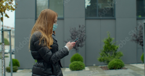 Fotografía Young redhead woman in protective medical mask walks down to the street uses phone texts scrolls surfs the internet