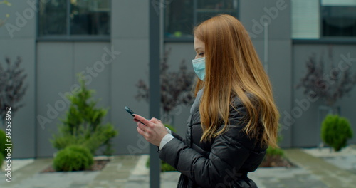 Cuadros en Lienzo Young redhead woman in protective medical mask walks down to the street uses phone texts scrolls surfs the internet