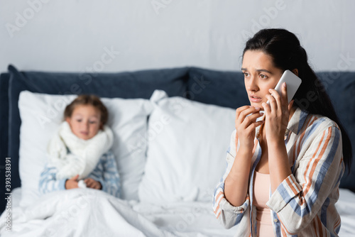 worried woman talking on mobile phone while sitting near ill child lying in bed Canvas Print