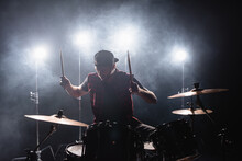 Rock Band Member Playing Drums While Sitting At Drum Kit With Backlit And Smoke On Background