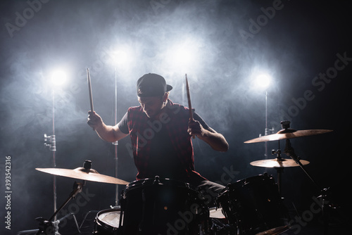 Fotografia Rock band member playing drums while sitting at drum kit with backlit and smoke