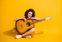 Full Size Photo Of Pretty Lovely Young Musician Girl Sit Hold Guitar Crossed Legs Country Music Star Wear Red Singlet Uncovered Shoulders Isolated Vibrant Yellow Color Background