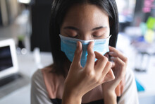 Close Up Of Asian Woman Wearing Face Mask Touching Her Nose At Modern Office
