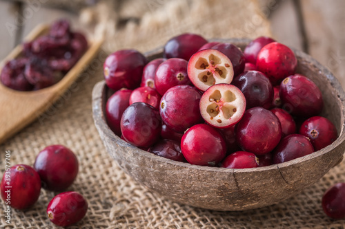 Raw cranberries in coconut shell on wooden table