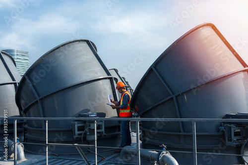 Canvas Print worker open valve of cooling tower on blue sky background