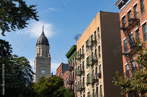 Church Steeple and Row of Colorful Old Residential Buildings with Fire Escapes i Fototapet