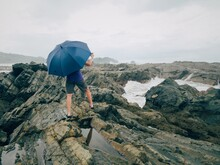 Rear View Of Woman With Umbrella Standing On Rock At Beach Against Cloudy Sky