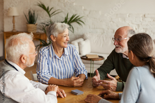 Obraz Group of four cheerful senior friends, two men and two women, sitting at table and enjoying talk after playing cards in assisted living home - fototapety do salonu