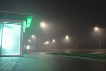Abandoned Kiosk Near A Street At Night, Covered By Slight Fog And Bright Green Neon Lights.