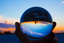Close-up Of Hand Holding Crystal Ball Against Blue Sky