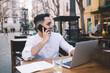 Positive ethnic male freelancer calling on cellphone