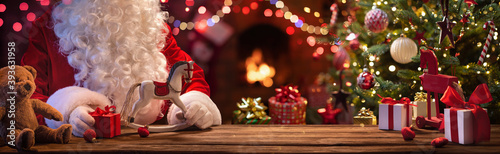 Santa Claus Sits At A Table With Gifts And Toys Near The Fireplace And Christmas Tree