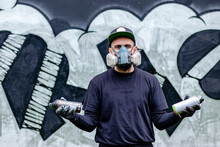 Graffiti Artist Posing In Front Of His Drawing On The Wall, With Two Aerosol Spray Paints In A Can, Wearing Protective Face Mask / Respirator With Filters. Street Art Culture Concept.