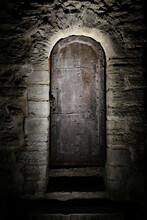 Medieval Door Close Up. Metal Entrance With Stone Steps. An Old Ancient Castle Fragment. Dark, Moody, Gothic Background. Mysterious And Secret Hidden Backdoor. Vertical, Low Key, Copy Space